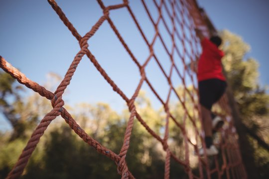 Boy climbing a net during obstacle course