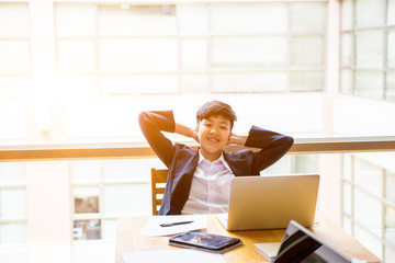 Asian short black hair tomboy business with two hand on head sit in front of laptop with smile on face.