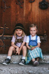 cute smiling children couple in typical austrian outfit sitting in front of wooden door