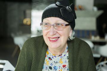 portrait of senior woman in  a cafթ