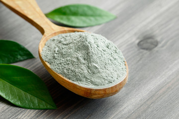 Close-up of a cosmetic dry gray clay in a wooden spoon on a black wooden table. Decorated with green leaves. Fototapete