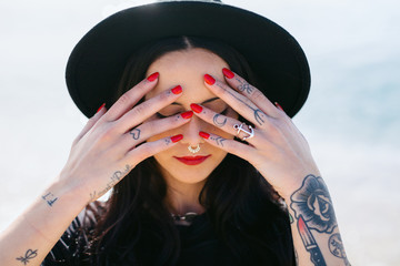 Young alternative woman with tattoos covering her eyes with hands