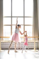Female ballet instructor teaching girl in ballet studio