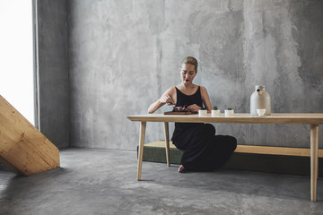 Woman Sitting and Pouring Herself some Tea