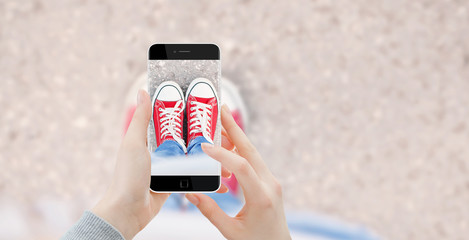 Girl taking photo with phone of her red shoes, top view