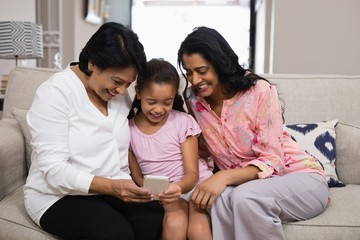 Happy multi-generation family using mobile phone