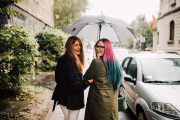 Two beautiful girlfriends walking under an umbrella