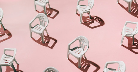Group of white chairs on pink background