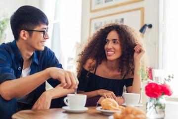 Happy trendy couple having breakfast in a coffee shop