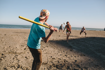 Friends play baseball on the beach