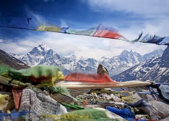 Snow-capped Himalayan mountain range viewed through flying tibetan prayer flags