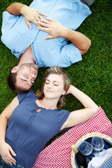 Overhead view of young couple lying on grass