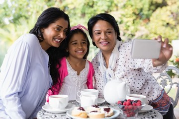 Family taking selfie while sitting by breakfast table