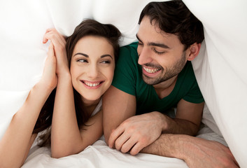 Young carefree couple laughing and enjoying morning in bed