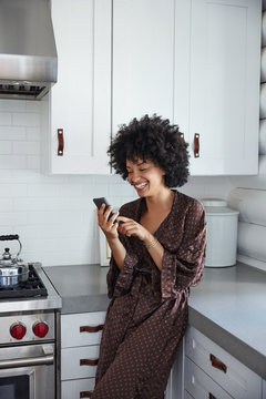 African American woman on her phone in kitchen