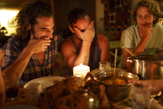 Friends sit around laughing and enjoying a dinner in candlelight