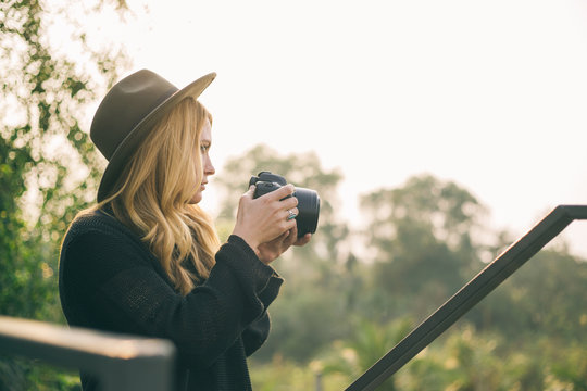 Blonde young woman taking photo of nature