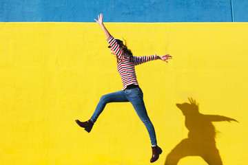 Happy young woman jumping in front of yellow background