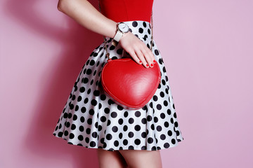 Wall Mural - Fashion small red bag in hand of girl . Polka dots skirt