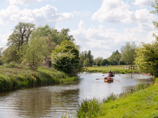people rowing boats down the river stour in dedham essex uk england in constable country