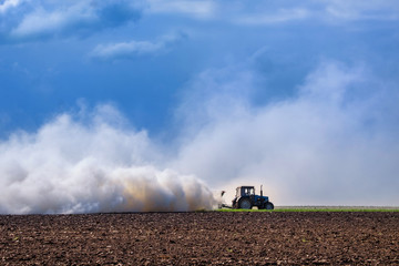tractor pulling plow, throwing dust up in the air. Tractor machine Cultivation field during agricultural works