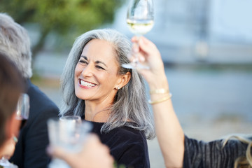 Portrait of senior woman with group of friends enjoying a Farm To Table Dinner Party in backyard
