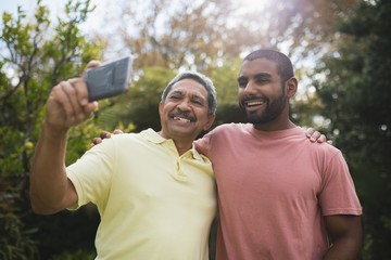 Happy father taking selfie with son at park