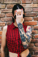 Young alternative woman with tattoos covering her face with a heavy metal sign
