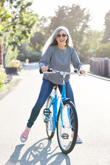 Portrait of stylish mature woman with grey hair riding a bike