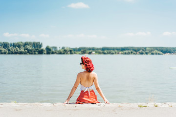 Young woman enjoying a sunny day at the river bank