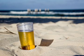 Glass of beer on beach sand