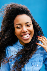 Young african woman laughing in front of a blue wall