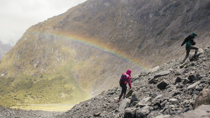 A couple of hikers climbs a rocky mountain with a rainbow in the background