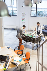 Businessmen playing table-football in a cool office