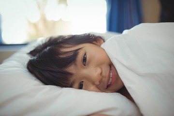 Smiling girl lying on the bed in bed room