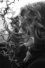 Profile of a beautiful woman with wavy hair beside the curly branches of a Hazel tree