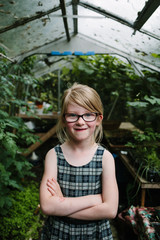 Portrait of cheeky girl wearing glasses with her arms crossed
