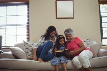 Mother and daughter reading book in living room