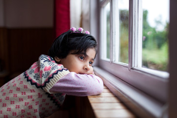 Little girl in a contemplative mood sitting by the window
