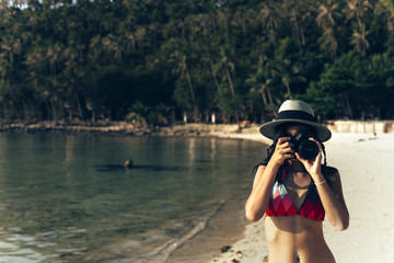 Woman in a Bikini Taking a Photo