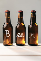 "The word ""beer"" written on three beer bottles"