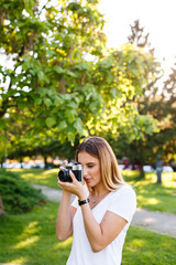 Young woman in park using her free time for photography