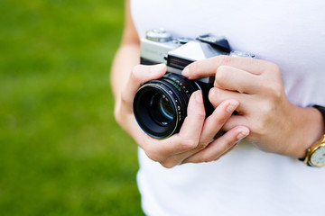 Hands of woman holding a camera on beautiful sunny day