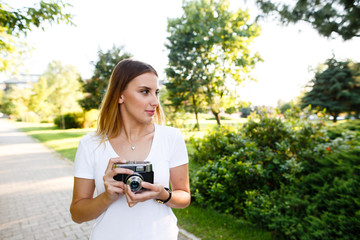 Attractive woman in park walking with her camera