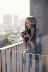 Beautiful girl looking at the city and holding her retro camera