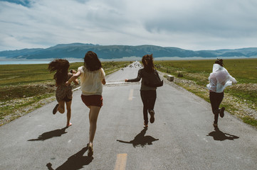 Four female running on the road