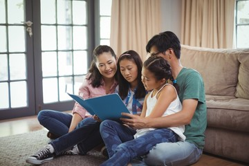 Family watching photo album together in living room