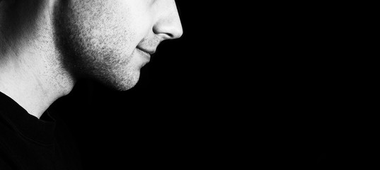 Profile of a guy with a bristles smiling on a black background, low key portrait
