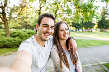 Cute and happy couple enjoying in park and taking selfie