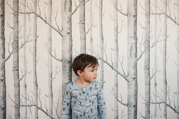 Cute little boy standing near tree wallpaper wearing pajamas